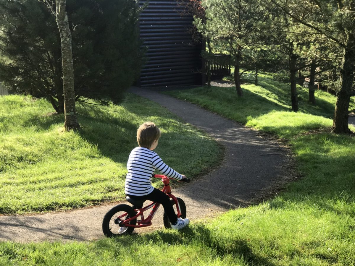 Dexter riding a red balance bike down a path outside our lodge in bluestone wales