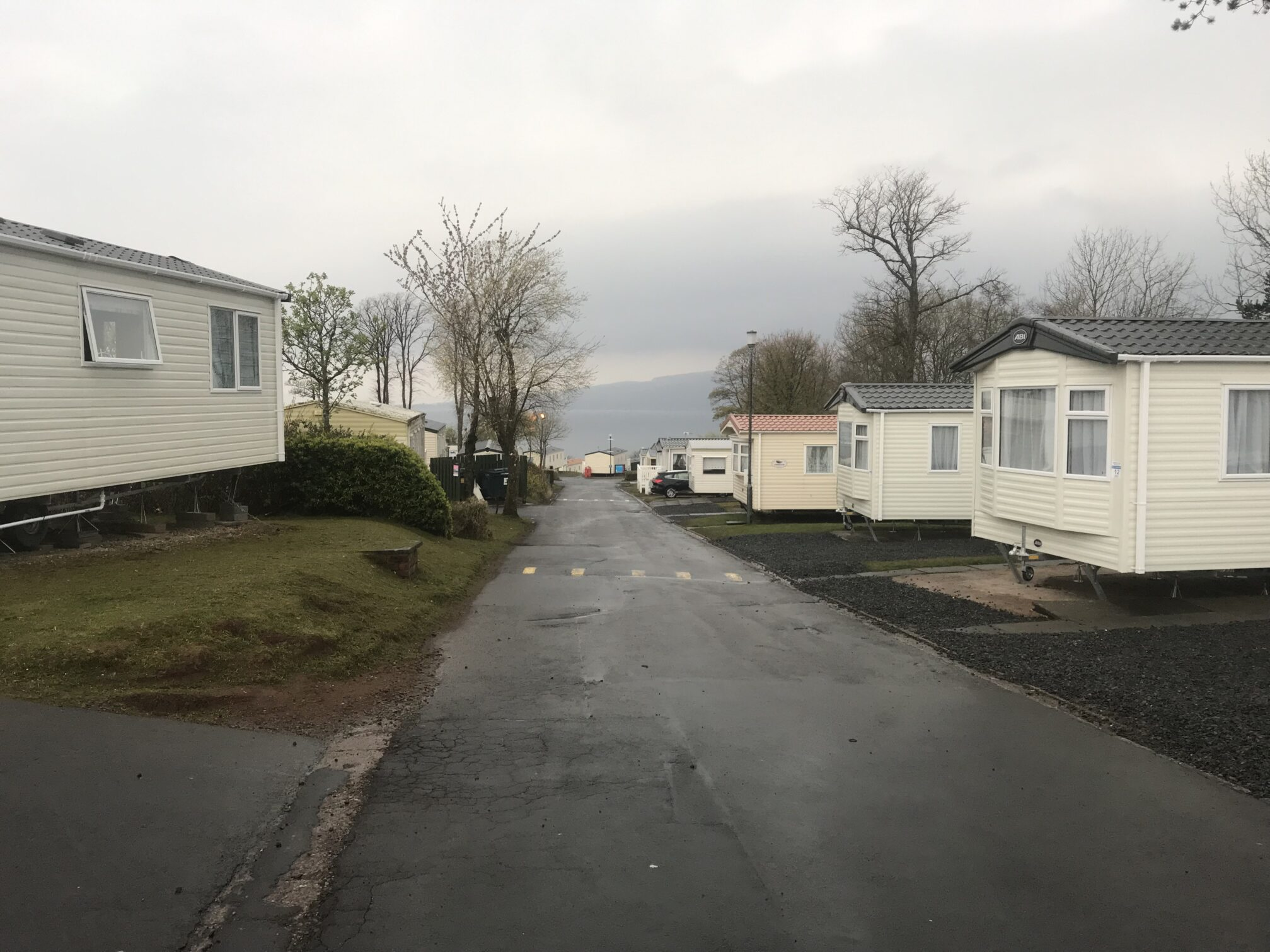 View down the road of Wemyss Bay cHoliday park showing caravans on both side and the firth of clyde ahead