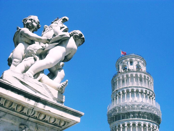 A shot of the top of the leaning tower of Pisa with a statue to the left