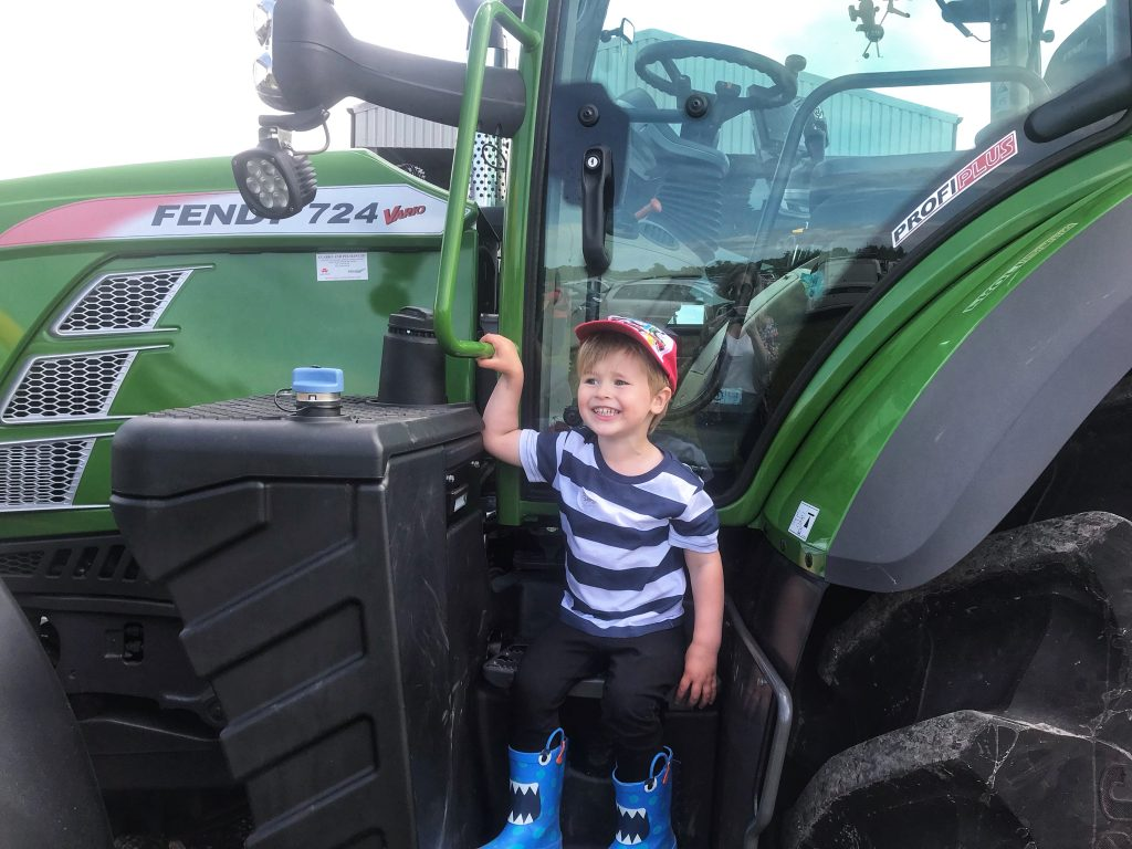 Dexter smiling sat on a green tractor in taylor's Farm on leaf Open farm sunday