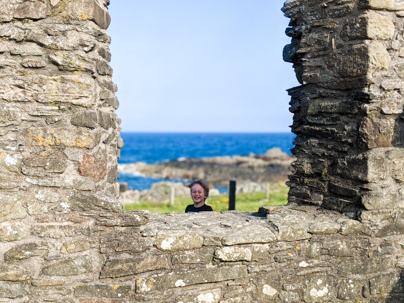 Dexter peeking through St Ninian's Chapel window with the sea behind him